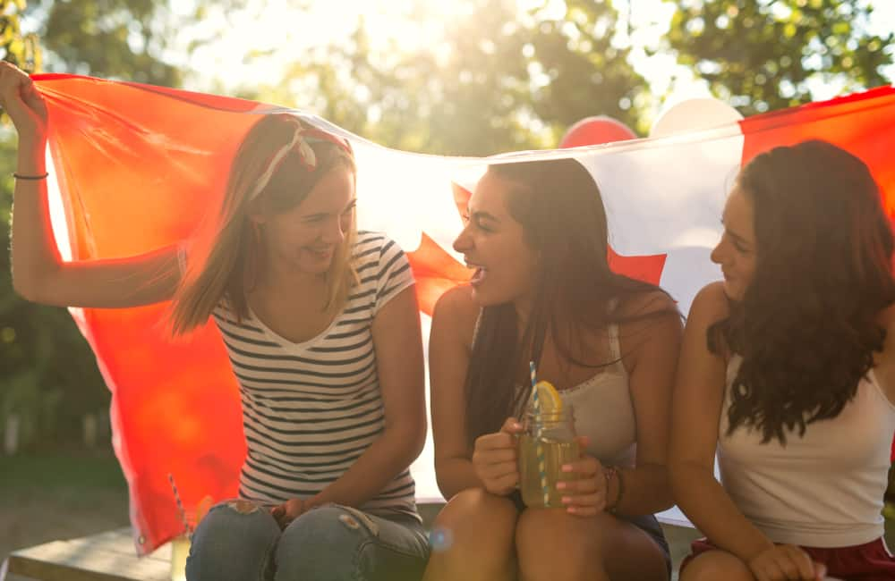 happy girls with Canadian Maple Leaf flag